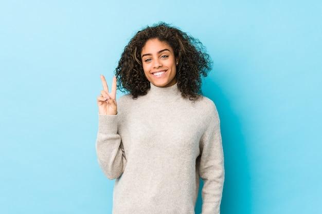 Jonge afrikaanse amerikaanse krullende haarvrouw die nummer twee met vingers toont.