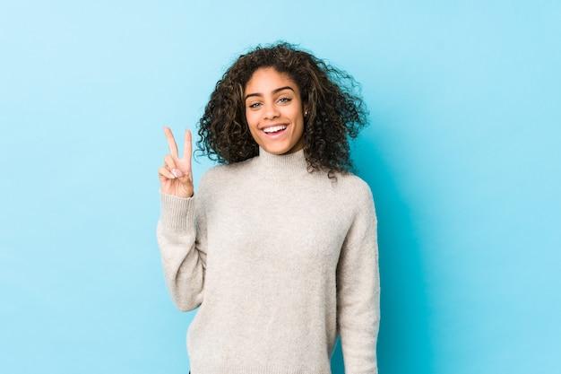 Jonge afrikaanse amerikaanse krullende haarvrouw die overwinningsteken toont en breed glimlacht.