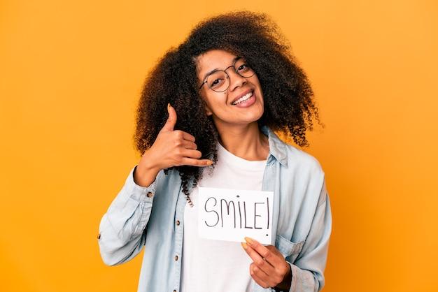 Jonge afrikaanse amerikaanse krullende vrouw die een aanplakbiljet van het glimlachbericht houdt dat een mobiel telefoongesprekgebaar met vingers toont.