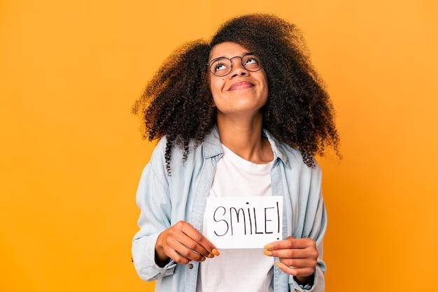 Jonge afrikaanse amerikaanse krullende vrouw die een aanplakbiljet van het glimlachbericht houdt van het bereiken van doelstellingen en doeleinden