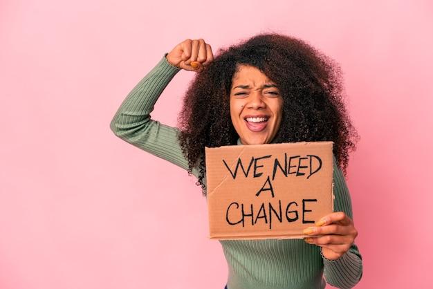 Jonge afrikaanse amerikaanse krullende vrouw die een houdt, hebben we een wisselkarton nodig dat vuist opheft na een overwinning, winnaarconcept.
