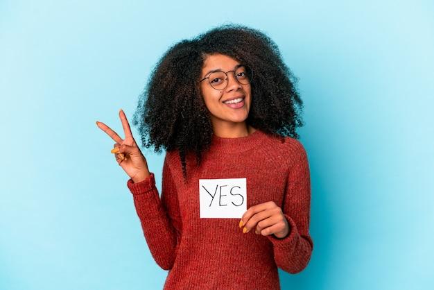 Jonge afrikaanse amerikaanse krullende vrouw die een ja aanplakbiljet blij en zorgeloos houdt dat een vredessymbool met vingers toont.