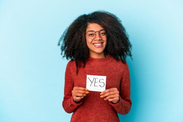 Jonge afrikaanse amerikaanse krullende vrouw die een ja aanplakbiljet gelukkig, glimlachend en vrolijk houdt.