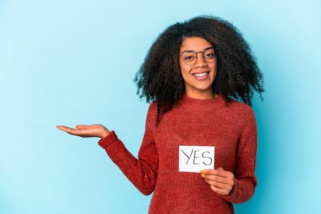 Jonge afrikaanse amerikaanse krullende vrouw die een ja aanplakbiljet houdt dat een exemplaarruimte op een palm toont en een andere hand op taille houdt.