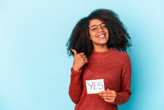Jonge afrikaanse amerikaanse krullende vrouw die een ja aanplakbiljet houdt dat en duim opheft