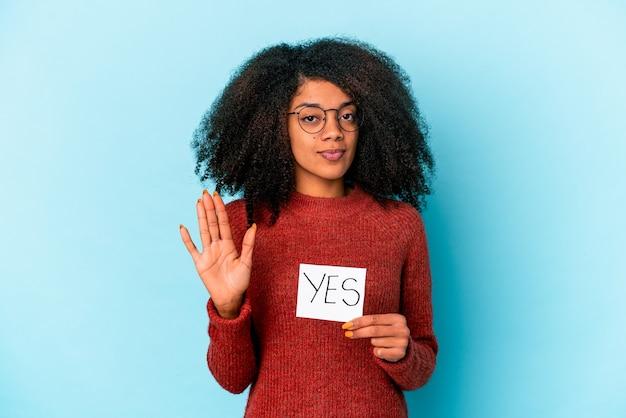 Jonge afrikaanse amerikaanse krullende vrouw die een ja aanplakbiljet houdt dat zich met uitgestrekte hand bevindt die stopbord toont, dat u verhindert.