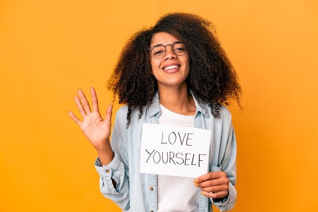 Jonge afrikaanse amerikaanse krullende vrouw die een liefde houden zelf aanplakbiljet vrolijk glimlachen tonend nummer vijf met vingers.