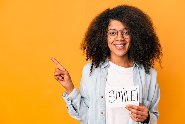 Jonge afrikaanse amerikaanse krullende vrouw die een plakkaat van het glimlachbericht houdt en opzij glimlacht wijst, iets op lege ruimte toont.