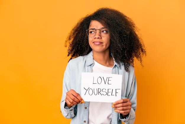 Jonge afrikaanse amerikaanse krullende vrouw die een plakkaat van liefde zelf houdt verward, voelt twijfelachtig en onzeker.