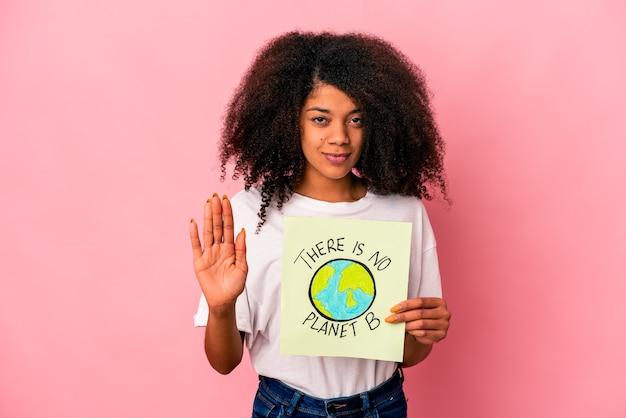 Jonge afrikaanse amerikaanse krullende vrouw die een planeetbericht op een aanplakbiljet houdt dat zich met uitgestrekte hand bevindt die stopbord toont, dat u verhindert.