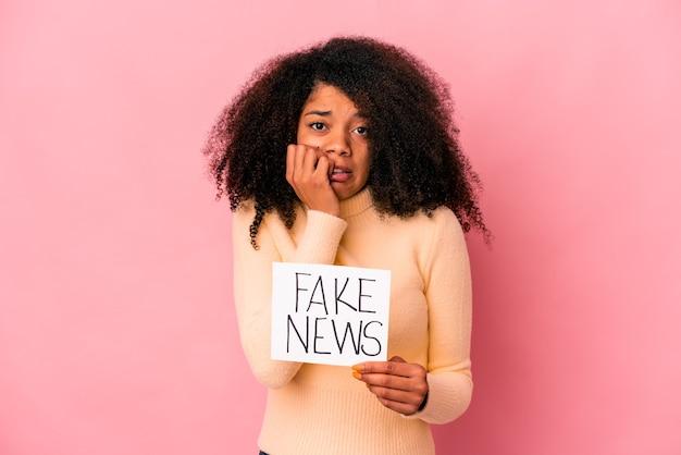 Jonge afrikaanse amerikaanse krullende vrouw die een vals nieuws op een plakkaat houdt die vingernagels bijt, zenuwachtig en zeer angstig.