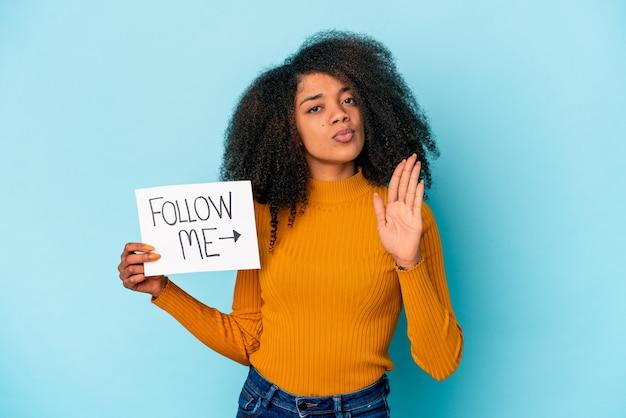 Jonge afrikaanse amerikaanse krullende vrouw die een volg-mij-plakkaat houdt dat zich met uitgestrekte hand bevindt die stopbord toont, dat u verhindert.