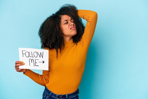 Jonge afrikaanse amerikaanse krullende vrouw die een volg-mij-plakkaat houdt die de achterkant van het hoofd aanraakt, denkt en een keuze maakt.