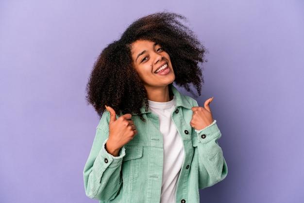Jonge afrikaanse amerikaanse krullende vrouw die op purpere achtergrond wordt geïsoleerd die beide duimen opheft, glimlachend en zelfverzekerd.