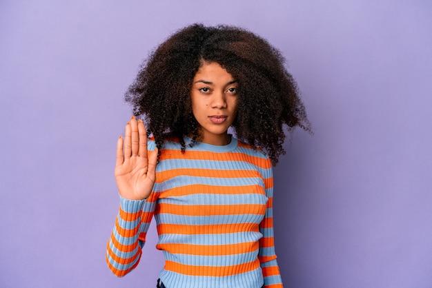 Jonge afrikaanse amerikaanse krullende vrouw die op purpere achtergrond wordt geïsoleerd die zich met uitgestrekte hand bevindt die stopbord toont, dat u verhindert.