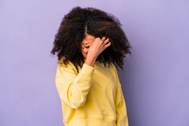 Jonge afrikaanse amerikaanse krullende vrouw die op purpere muur wordt geïsoleerd, die hoofdpijn heeft, de voorkant van het gezicht aanraakt.