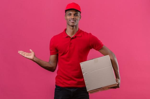 Jonge afrikaanse amerikaanse leveringsmens die rood poloshirt draagt en kartondoos houdt en iets voorstelt dat hand aan de kant over geïsoleerd roze richt