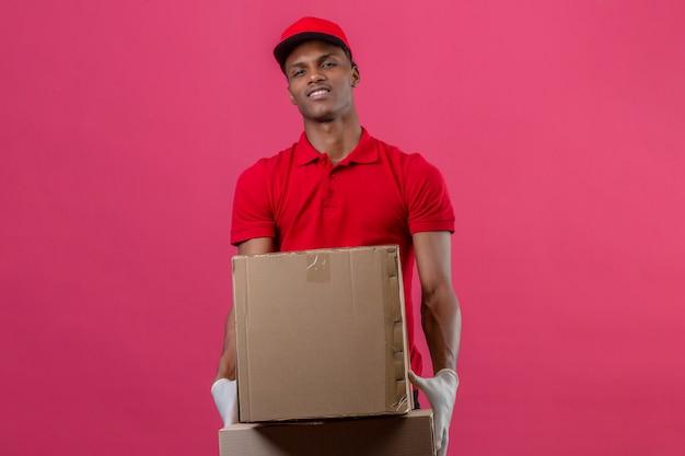 Jonge afrikaanse amerikaanse leveringsmens die rood poloshirt en glb dragen die de zekere dozen van het holdingskarton met glimlach op gezicht over geïsoleerd roze kijken