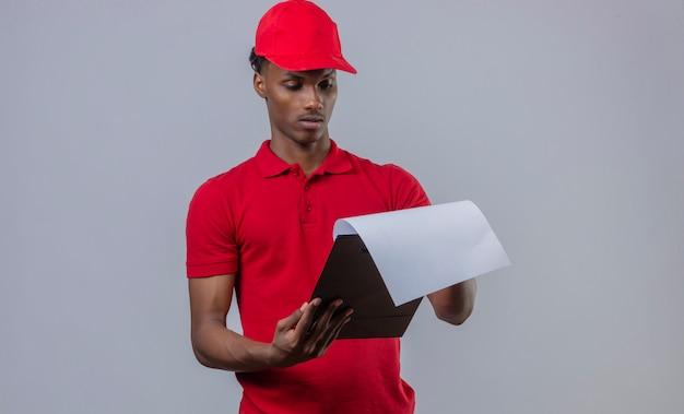 Jonge afrikaanse amerikaanse leveringsmens die rood poloshirt en glb dragen die klembord met ernstig gezicht over geïsoleerd wit bekijken