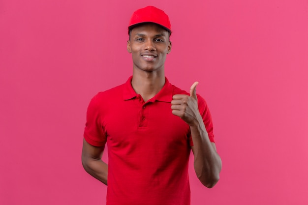 Jonge afrikaanse amerikaanse leveringsmens die rood poloshirt en glb met glimlach op gezicht dragen die duimen over geïsoleerd roze tonen