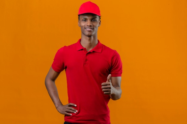 Jonge afrikaanse amerikaanse leveringsmens die rood poloshirt en glb met glimlach op gezicht dragen die duimen tot camera over geïsoleerde sinaasappel tonen