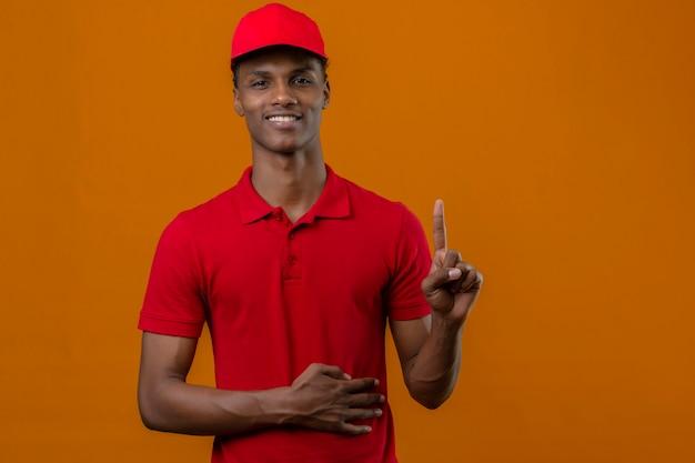 Jonge afrikaanse amerikaanse leveringsmens rood poloshirt dragen en glb die zich met glimlach op gezicht bevinden die vinger over geïsoleerde sinaasappel benadrukken