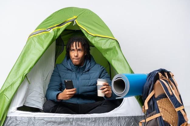 Jonge afrikaanse amerikaanse mens binnen een het kamperen groene koffie van de tentholding om weg te nemen en mobiel terwijl het denken van iets
