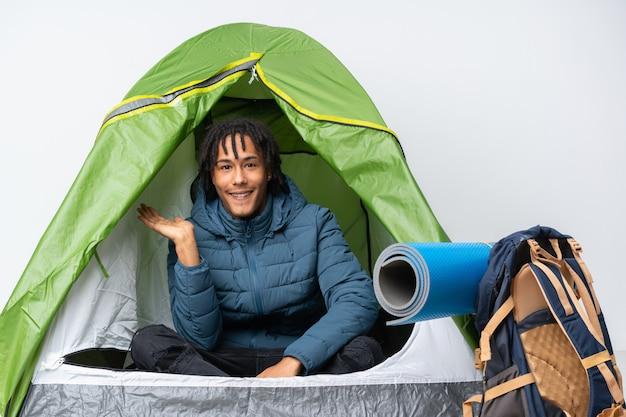 Jonge afrikaanse amerikaanse mens binnen een het kamperen groene tent die copyspace denkbeeldig op de palm houdt om een advertentie op te nemen