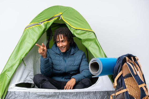 Jonge afrikaanse amerikaanse mens binnen een het kamperen groene tent die vinger aan de kant richt en een product voorstelt