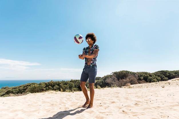 Jonge afrikaanse amerikaanse mens die bal op strand werpt