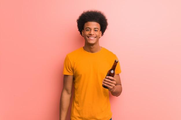 Jonge afrikaanse amerikaanse mens die een bier met een grote glimlach vrolijk houdt
