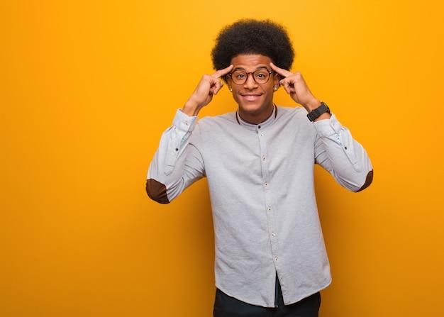 Jonge afrikaanse amerikaanse mens die een concentratiegebaar doet