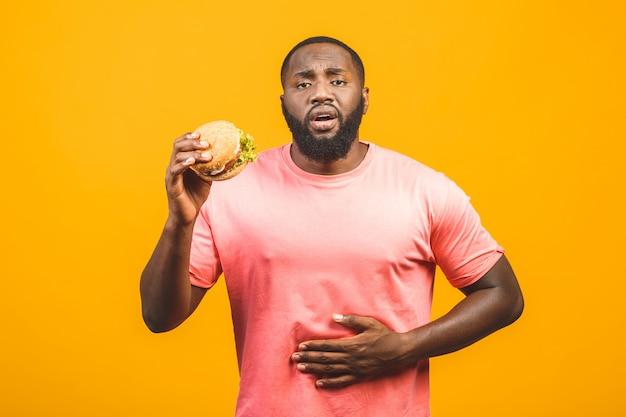 Jonge afrikaanse amerikaanse mens die hamburger eet die over gele muur wordt geïsoleerd.