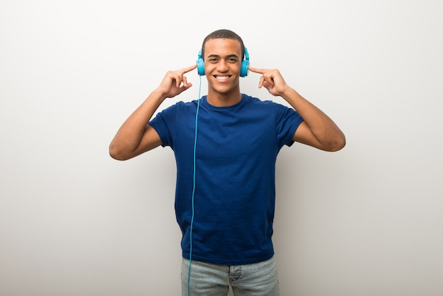 Jonge afrikaanse amerikaanse mens die op witte muur aan muziek met hoofdtelefoons luistert