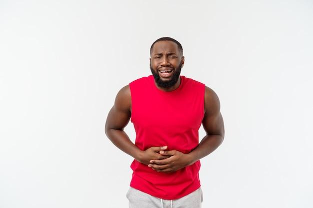 Jonge afrikaanse amerikaanse mens die sportslijtage met hand op maag draagt omdat misselijkheid, pijnlijke ziekte onwel voelen.