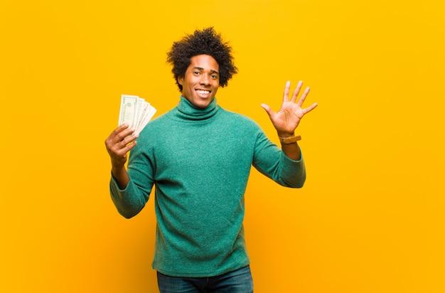 Jonge afrikaanse amerikaanse mens met dollarrekeningen tegen oranje rug