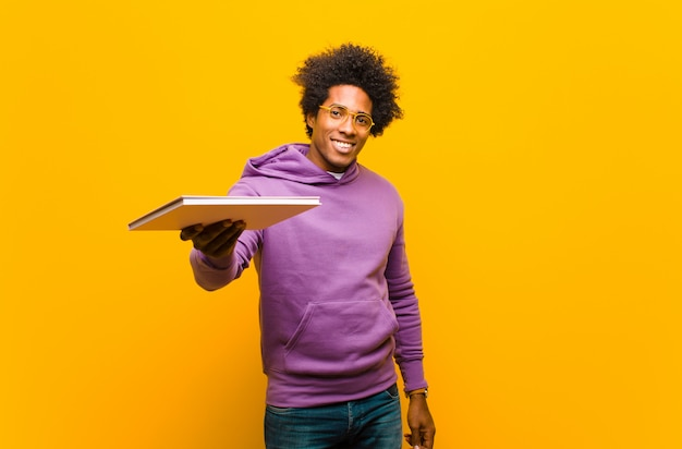 Jonge afrikaanse amerikaanse mens met een boek tegen oranje achtergrond