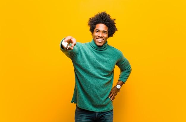 Jonge afrikaanse amerikaanse mens met een creditcard tegen oranje bac
