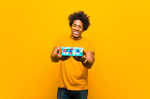 Jonge afrikaanse amerikaanse mens met een giftdoos tegen sinaasappel