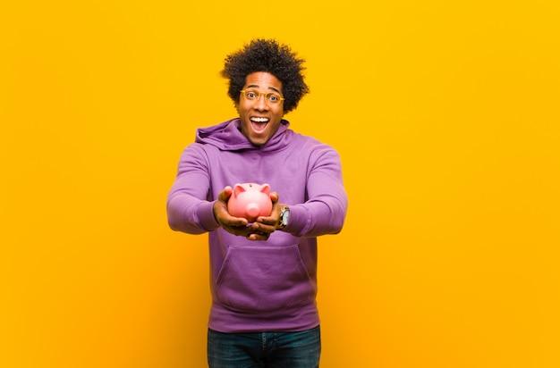Jonge afrikaanse amerikaanse mens met een spaarvarken tegen oranje rug