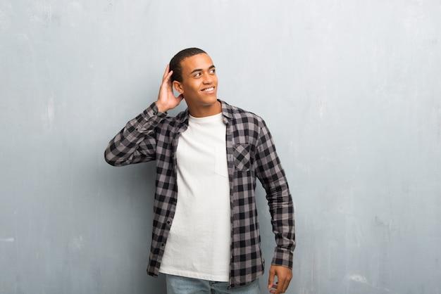 Jonge afrikaanse amerikaanse mens met geruit overhemd die een idee denken terwijl het krassen van hoofd