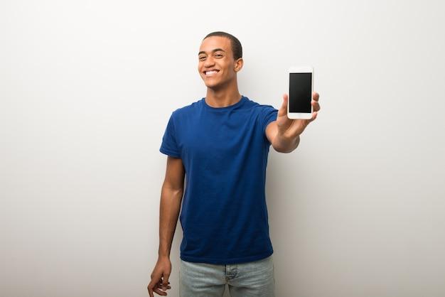 Jonge afrikaanse amerikaanse mens op witte muur die mobiel toont