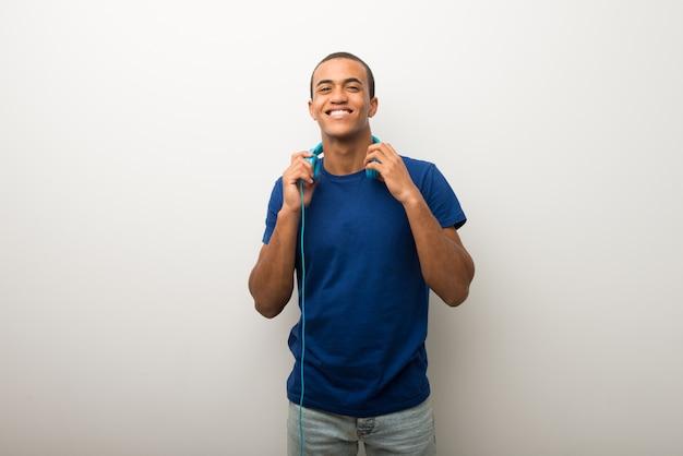 Jonge afrikaanse amerikaanse mens op witte muur met hoofdtelefoons