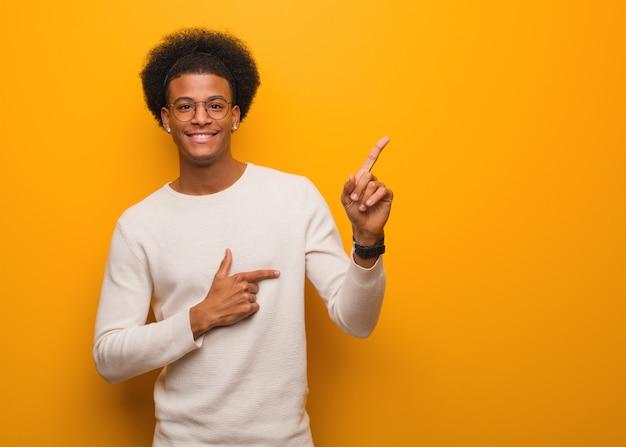 Jonge afrikaanse amerikaanse mens over een oranje muur die aan de kant met vinger richt