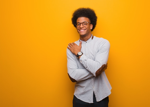 Jonge afrikaanse amerikaanse mens over een oranje muur die een omhelzing geeft