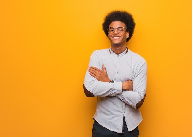 Jonge afrikaanse amerikaanse mens over een oranje muur die wapens kruisen, glimlachen en ontspannen