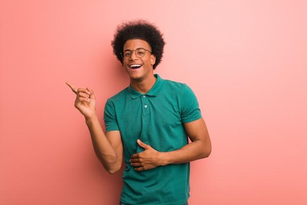 Jonge afrikaanse amerikaanse mens over een roze muur die aan de kant met vinger richt