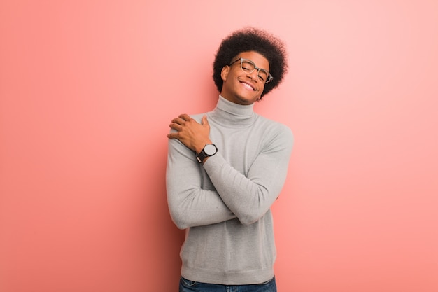 Jonge afrikaanse amerikaanse mens over een roze muur die een omhelzing geeft