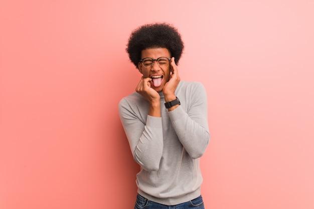 Jonge afrikaanse amerikaanse mens over een roze wanhopige en droevige muur