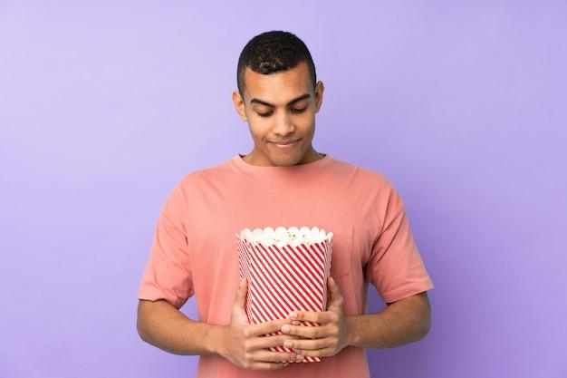 Jonge afrikaanse amerikaanse mens over geïsoleerde blauwe muur die een grote emmer popcorns houdt